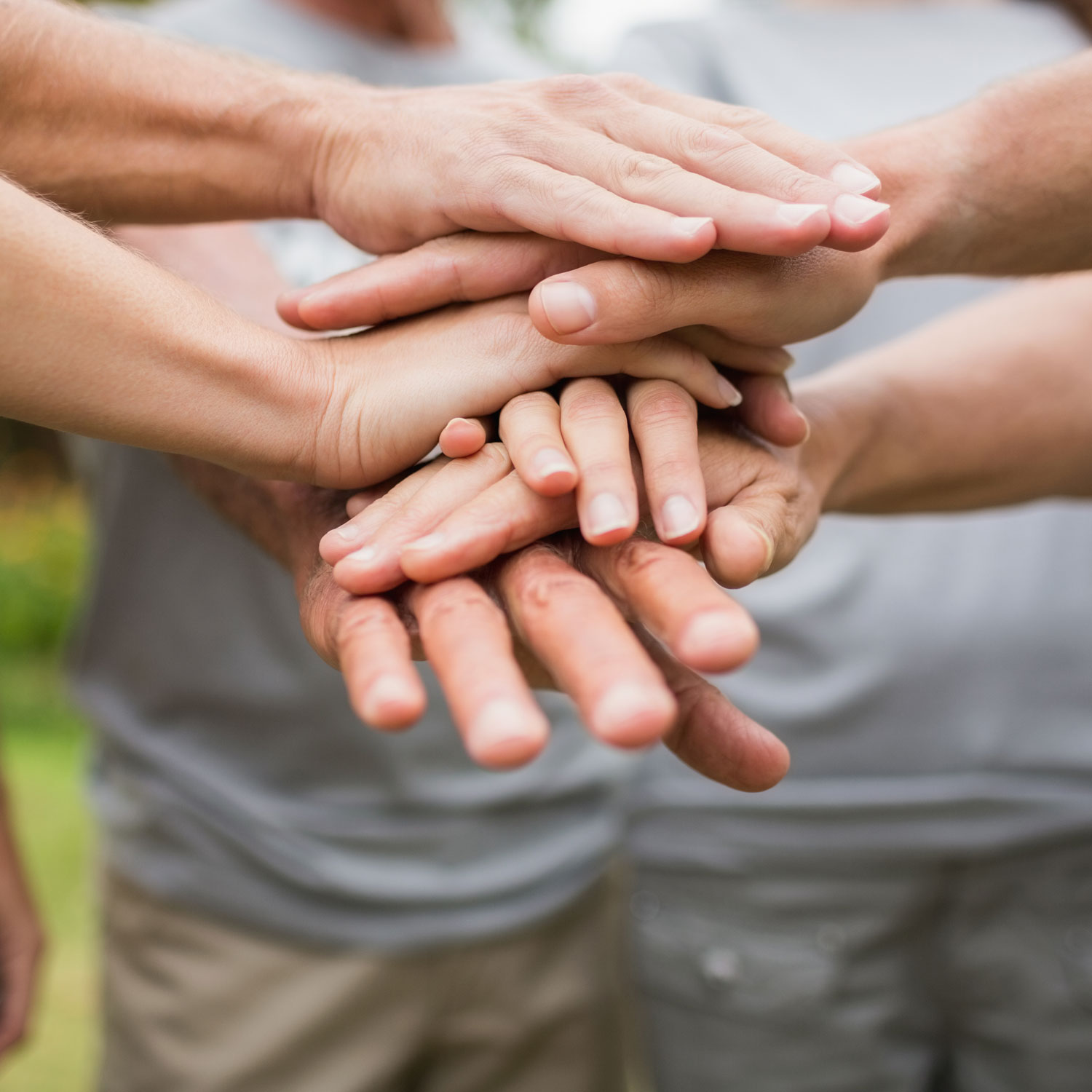 People in a circle stacking hands.