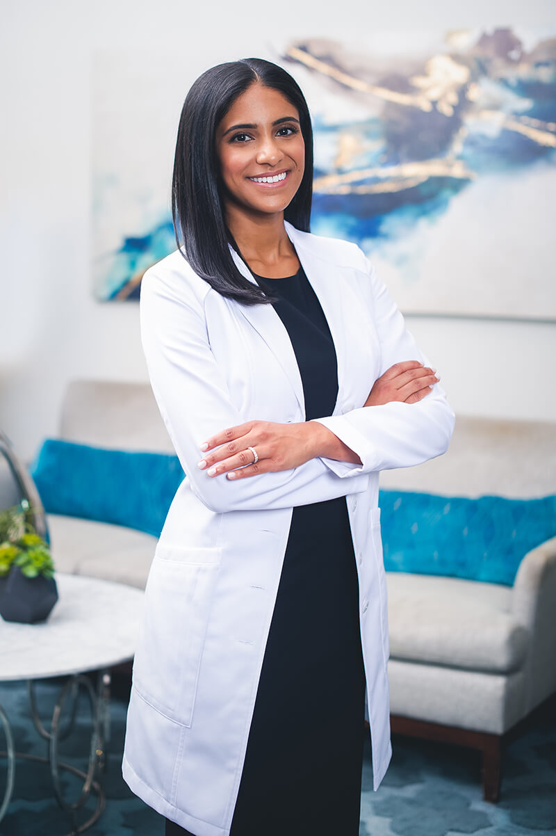 Dr Amy Hassan standing with arms crossed in a white jacket and blue dress
