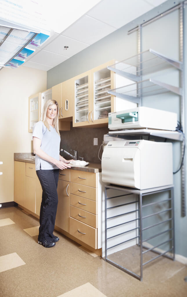 A dental assistant standing at a counter cleaning tools