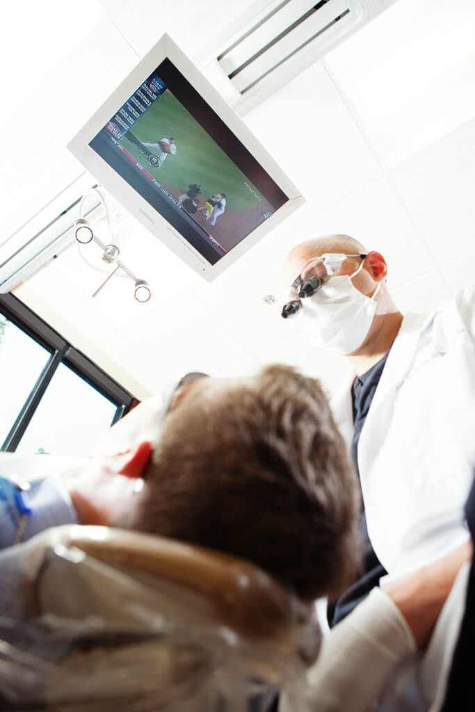 A patient in a comfortable dentist chair watching a tv on the ceiling