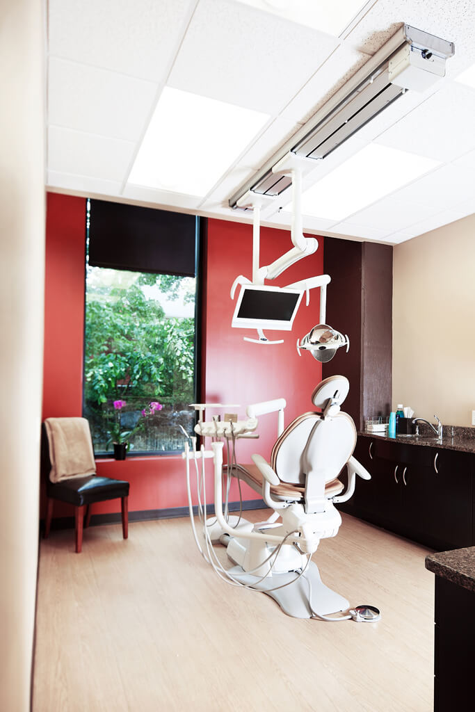 A dental suite with red walls and hardwood floor.