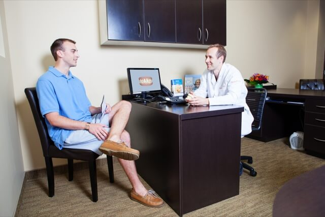 Our doctor consulting with a patient in an office with a computer
